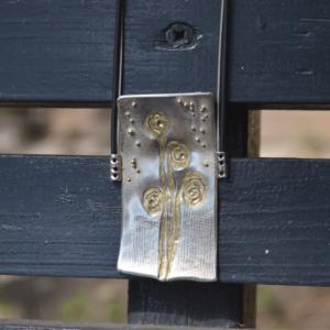 Zilveren hanger met bloemenlandschap en gouden bolletjes