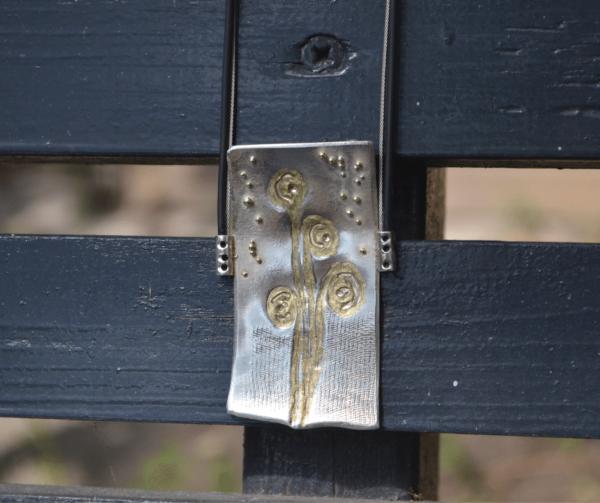 Zilveren hanger met bloemenafdruk en gouden bolletjes