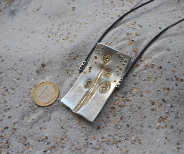 Hanger van zilver met bloemenafdruk en gouden bolletjes