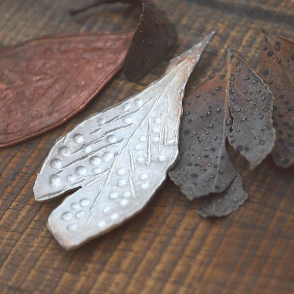 afdruk van een verweerd blad in zilver